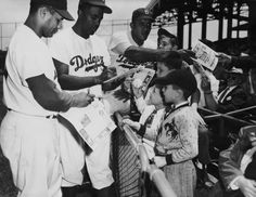 Brooklyn Dodgers signing autographs (L to R): Roy Campenella, Jackie Robinson and Don Newcombe (circa 1949) // @Library of Sew Angeles Dodgers