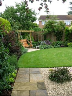 lawn framed by shrubs and trees, corner swing, stone path. really nice