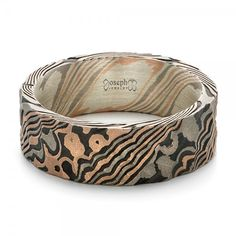 #102265 This stylish men's wedding ring features a lovely mokume gane pattern, which is enhanced by the acid etching and hammered finish. It was created for a client based in...
