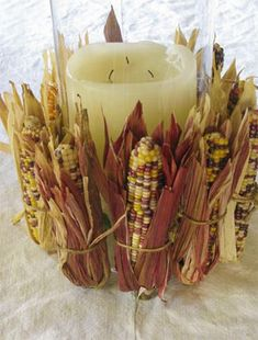 Add colorful corn in husks around a flameless candle for a natural gorgeous addition to the pumpkin centerpiece. #RobinBaron