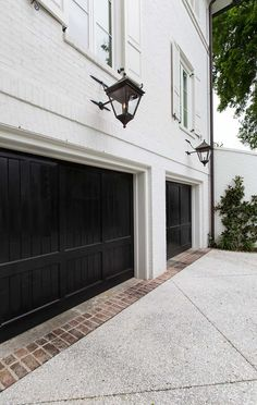 Double black garage doors, white brick, UEC fixtures