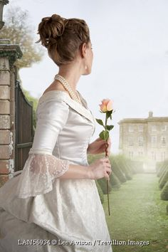 Trevillion Images - woman-with-rose-by-country-house