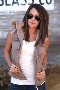 Long brunette hair with subtle highlights. Casual outfit with sunglasses.