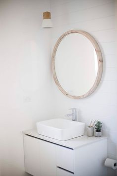 COASTAL BATHROOM Paneling and round mirror