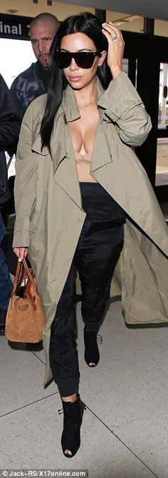 Kim Kardashian shows ample cleavage in plunging nude top at LAX #dailymail