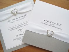 Albany Wedding Invitations in white and silver and finished with white ribbon and a crystal heart.