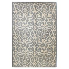 Offering an artful anchor for a vibrant space or touch of texture in your living room or den, this beautifully hand-tufted wool rug features an ornate transi...