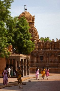 India, Thanjavur. Colourful sarees contrast with the ornate carvings of the Brihadeeswarar Temple.