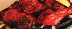 Fresh chicken legs cooked in oven and marinated in a sauce mixed with yogurt and fresh spices, garlic, and ginger.