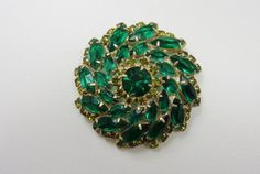 This is a lovely vintage emerald green clear rhinestone brooch. This brooch is from the 40'-50's era It is made up of marquis shaped emerald green stones.  And has small li...