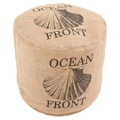 Bring a touch of beach house style to your living room or den with this lovely jute-upholstered pouf, showcasing a shell motif with typographic details.