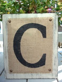 Sharpie Letter onto burlap. Tack to piece of wood.
