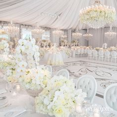 White on white wedding reception decor.  Notice the floral detail on the chandelier over the monogrammed dance floor.  Elegance taken to another level