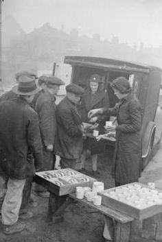 Rachal Bingham sets up mugs ready to start selling cups of tea and buns to people helping to clear up damage and debris in this bombed area of London. Patience 'Boo' Brand stands behind Rachel, in front of the tea car, where a counter has been set up. Vintage London, Old London, Women In History, British History, Ww2 Pictures, Vintage Pictures, Vintage Images, Coventry Blitz, Home Guard