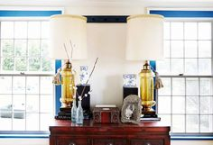 A pair of gold lamps set a top a red wood dresser