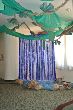 "Our 8 ft waterfall welcomed the kids into the sanctuary. Plastic table cloths bunched and hung from a frame, foil background from Oriental Trading, & Christmas lights behind made it sparkle. Fabric & paper bag rocks completed the look. A boom box behind with a ""jungle waterfall"" track (iTunes) playing gave great sound effects."