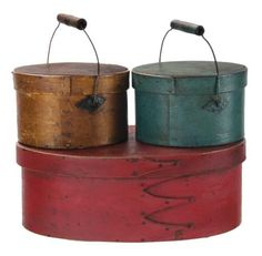 Lot 89: Three Boxes.  Estimate: $1K – $2K.  Price Realized: $1,416.  Oval box, maple and pine, early bright lipstick red painted finish over a dark stain, four fingers, copper nails and tacks, 3 3/4″ h, 9 1/8″ l; Two round lidded boxes, copper nails and wooden pegs, both with wire bails and small turned birch handles, raised diamond shaped bail plates, original brown stained varnish finish, and original dark turquoise blue painted finish with patina, 2 7/8″ h, 5″ h (to top of handle), 4 1/2″…