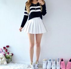 A black sweater with white stripes, featuring a white pleated skirt and #Adidas Superstar sneakers.