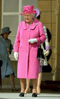 Queen Elizabeth II is a vision in vibrant pink as she arrives for the garden party held at Buckingham Palace