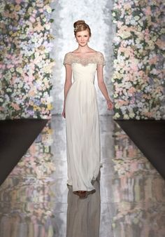 Silk Moroccan sheath wedding gown features sophisticated crisscrossed ruching on the bodice, and illusion cap sleeves with portrait neckline and Art Deco Diamante detailing.