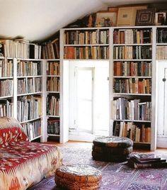 Bookshelves, leather pouf, awesome rug, cool little sofa. Dream home, fo sho!