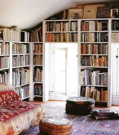 Bookshelves, leather pouf, awesome rug, cool little sofa. Dream home, fo sho!