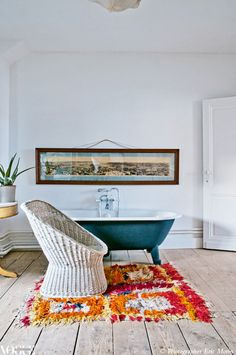 Colour is injected into this bathroom through the placement of a bright orange and pink shag rug in front of the freestanding bathtub.
