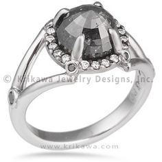 Raw Claw Engagement Ring - This edgy engagement ring was designed for a rose-cut raw diamond. The center stone is secured by claw-like prongs, and a halo of paved diamonds surround it. The shank splits and is adorned with accent stones.
