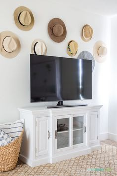 Cute idea for decorating around a TV. These beach hats are a fun way to add personality and memories to the wall! #bohodecor #coastaldecor #coastallivingroom