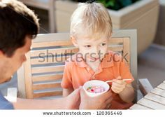 father and his son eating ice-cream in outdoor cafe - stock photo