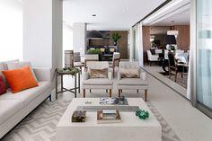 Sala de estar com móveis brancos, almofada laranja e porta de correr.