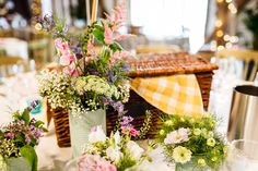 Picnic basket & gingham blanket with spray painted tin cans filled with wild flower stems - An outdoor DIY wedding ceremony in Cambridgeshire England with bright blue colour scheme, huge balloons, many rustic home made touches, dress by Allure Bridals