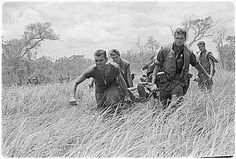 Vietnam War...Marines under heavy firefight carry a wounded fellow Marine to the evacuation helicopter.