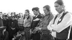 AIM Oglala Sioux Indians observe the Department of Justice's decision to remove government forces from around Wounded Knee with a ceremonial peace pipe smoking, March 10, 1973. Pictured are AIM leaders Dennis Banks (in beret), Russell Means (with pipe) and Carter Camp.  Photo credit: Associated Press