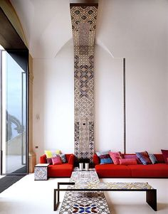 Tiled features, colourful cushions, high ceilings, huge bifold glass doors... a very regal space. Not sure who the designer is.