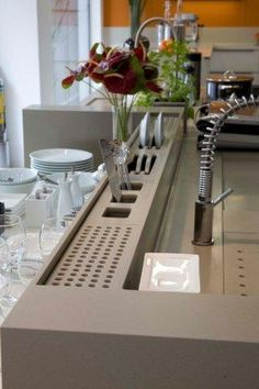 en el area del fregadero, detras de la pluma, se le puede monter unos bloques para que sean escurridor de cucharas tapando la parte que va a estar abajo y abrir mellas para los platos