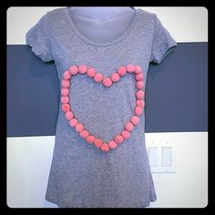 "💕T-shirt with pink pom-pom heart! 💕 NWOT Pink pom pom heart gray t-shirt. Pom Pom are on trendy this season!!! Throw this cutie on with jeans and boots! You surely will catch some eyes with this playful top!!!  Crop Brand new no tags Size small Bust is approx 16"" side to side, waist is approx 15"" side to side and the bottom is approximately 17"" side to side.  The length is 25"" L.K.Collections Tops Tees - Short Sleeve"