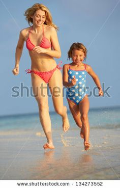 Mother And Daughter Having Fun In Sea On Beach Holiday - stock photo