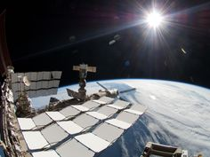 The bright sun, a portion of the International Space Station and Earth's horizon are featured in this image photographed during the STS-134 mission's fourth spacewalk in May 2011. The image was taken using a fish-eye lens attached to an electronic still camera.