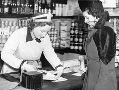 A shop assistant cuts a coupon from a London woman's ration book Dec. 14, 1940.