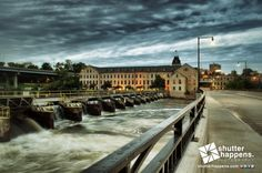 An Evening Down In The Flats by Mark David Zahn Photography (formerly Shutter Happens Photography).  The early glow of the streetlamps illuminates the new Olde Oneida Street bridge over the Fox River in Appleton, Wisconsin.
