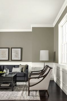 Deep gray contrasts against the sharp white lines of wainscoting and trim in a contemporary living room. | Driftwood Grey, @gliddenpaint