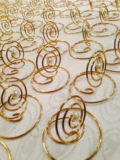 These will ship within 4 - 6 weeks ( if you need them sooner, please let me know and Ill do what I can to meet your deadline)   Dont let the size fool you.... Lightweight and flexible, these can be used for placecards, table number markers and menu card holder, more ideas mentioned below. Will hold a 4 x 6 nicely. (not recommended for outdoors on breezy days)  Gold or Silvertone Swirl Wire Art Card Holders, each are hand crafted and extremely versatile, accented with a pearl to add a bit of…