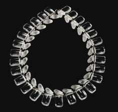 A molded, frosted glass and metal necklace by René Lalique. The design was made in 1929, but not produced until after 1947.