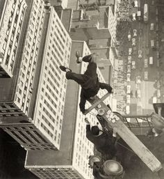 A man balancing on a piece of wood on the roof of a skyscraper 1939 ny