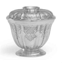 A GEORGE II SILVER SUGAR BOWL AND COVER MARK OF PEZE PILLEAU, LONDON, 1740 Of rice-bowl form on a molded circular base, with alternating ogee-fluted sides and cover, the body and cover flat chased with rocaille decoration including shells, scrolls and foliage, the cover with collet foot and engraved with a crest