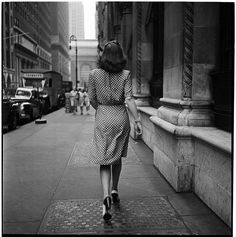 Photo by Stanley Kubrick of a woman in a polka dot dress and heels striding away from the camera. 1940s