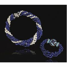 Necklace composed of five strands of round sapphire beads and two semi-baroque pearls.  Clasp of white gold and diamonds--signed Birks.  Bracelet of six round sapphire beads, clasp yellow gold, encrusted with beads and accented with blue enamel. Signed Verdura.