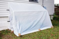 This DIY fold-down greenhouse made of PVC pipe and plastic, folds down to protect plants during cold snaps, then can be raised up on warmer days.