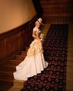 Creamy steampunk wedding gown complete with ivory lace, a top hat, a bouquet, and a gorgeous gold corset. Beautiful.